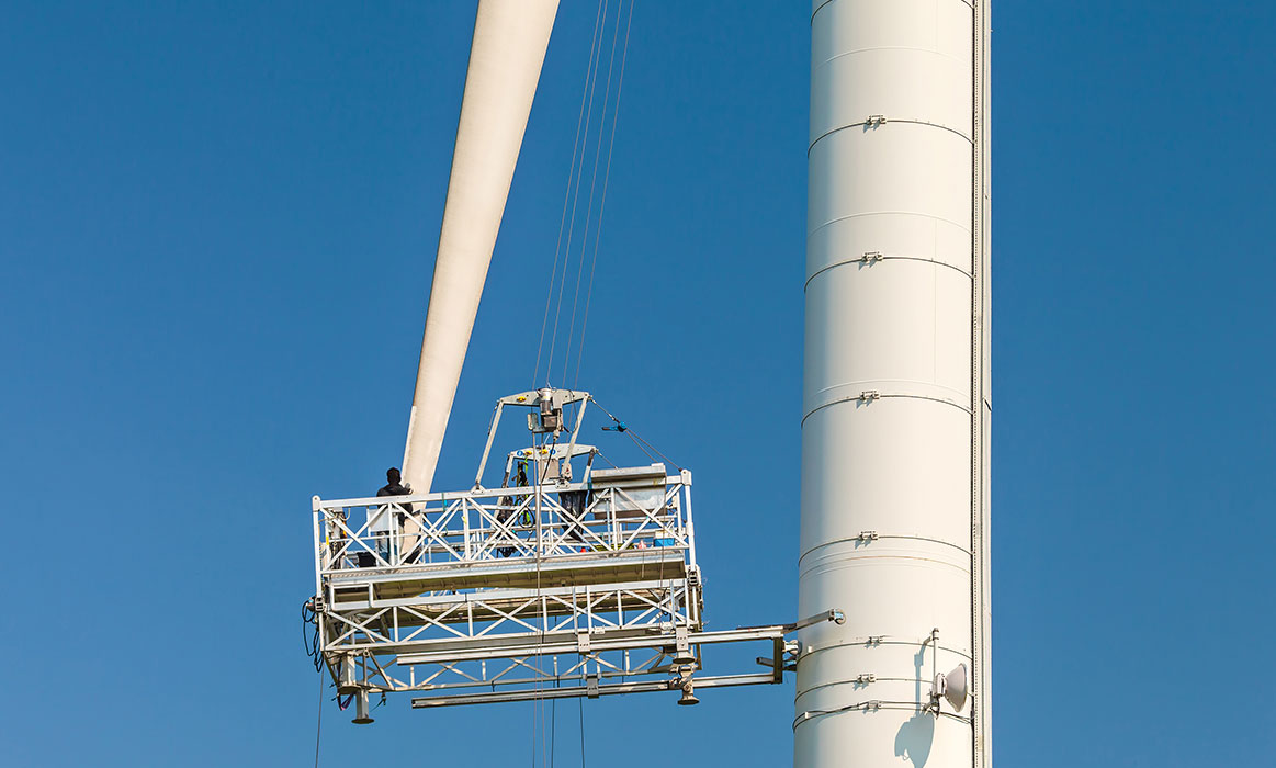 Technicians on a lift outside a wind turbine elevator shaft, inspecting installation of the propellor