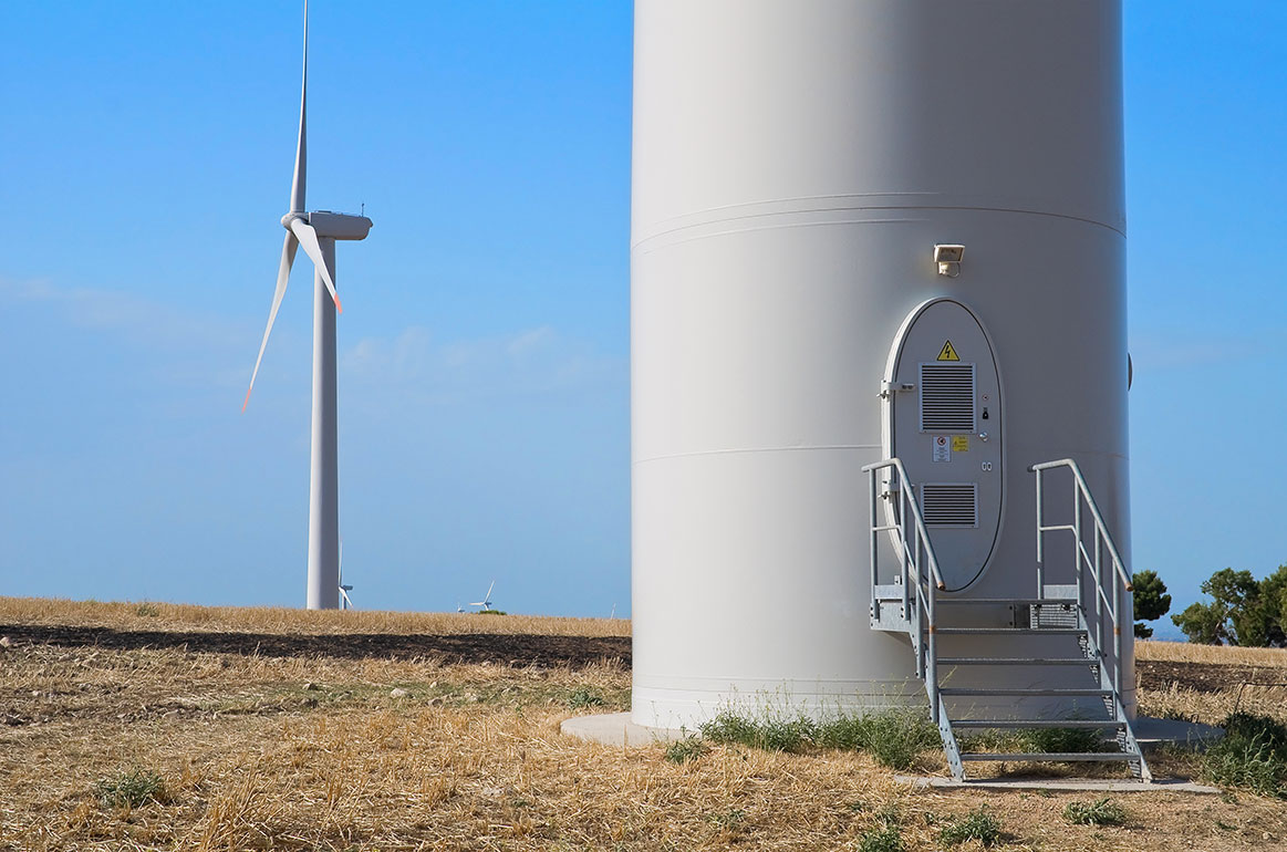 View of the door to a wind turbine elevator column with another wind turbine in the distance.