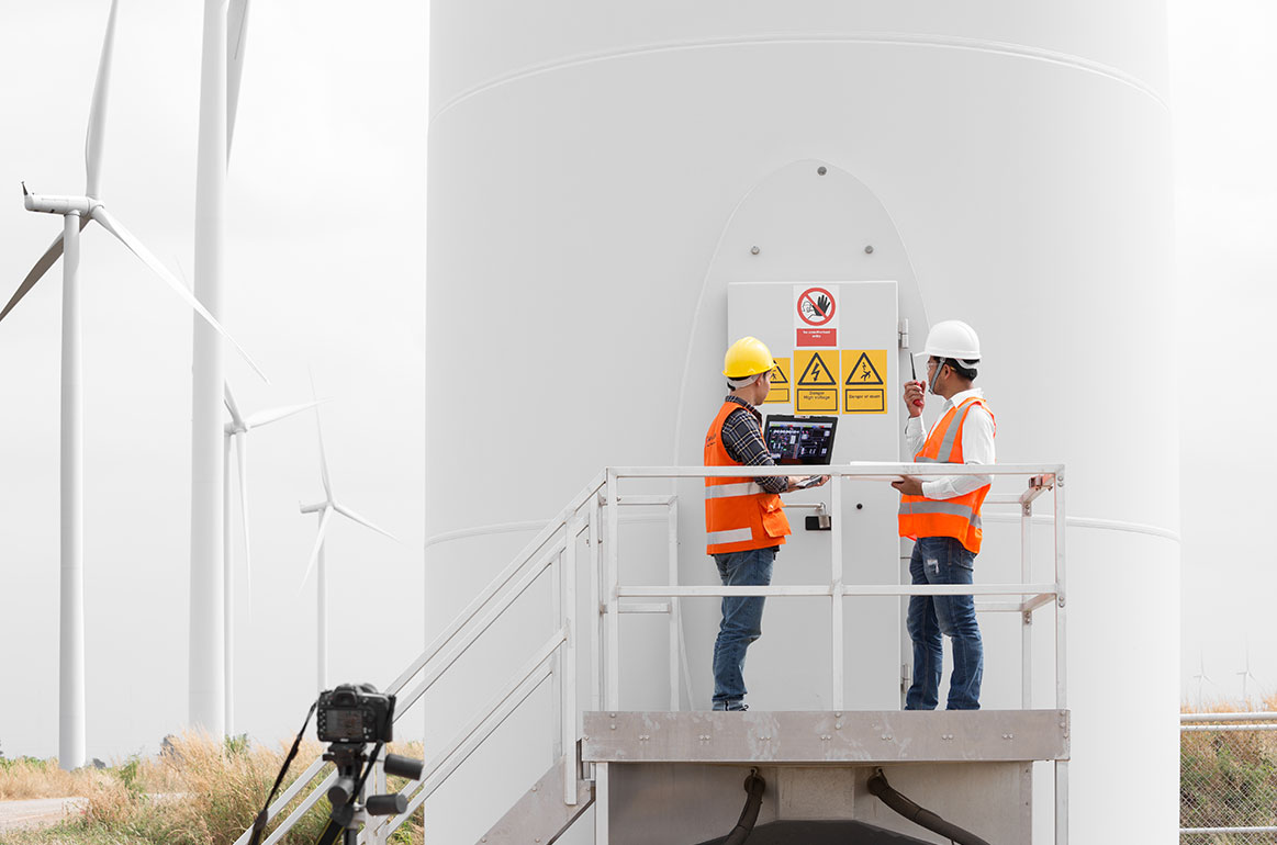 Two wind turbine elevator technicians inspecting the turbine on site.