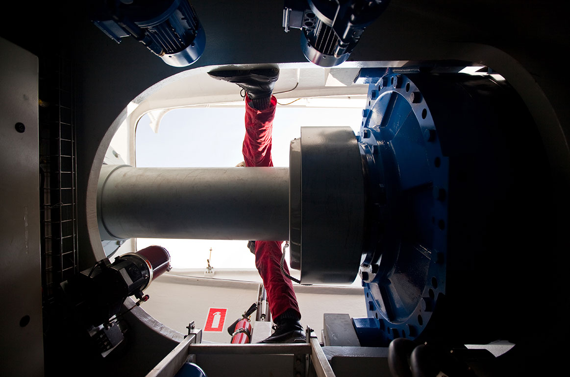 View of wind turbine technician working on the propellor from below.